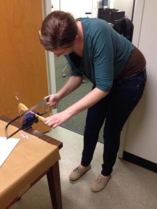 Making a padded hanger: Sawing a wooden hanger to make it fit a child's suit.